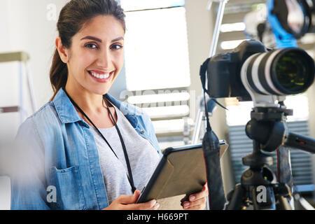 Portrait smiling female photographer using digital tablet behind camera in studio - Stock Photo