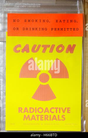 Radioactive material warning sign on laboratory door. - Stock Photo