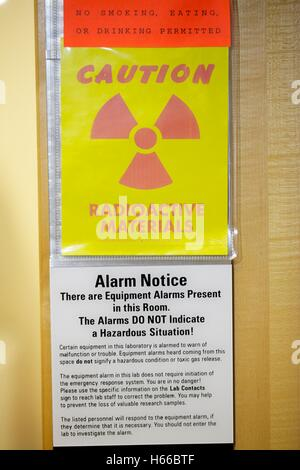 Radioactive material warning sign and alarm notice on laboratory door - Stock Photo