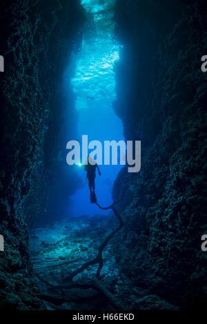 Scuba diver enters underwater cave system - Stock Photo