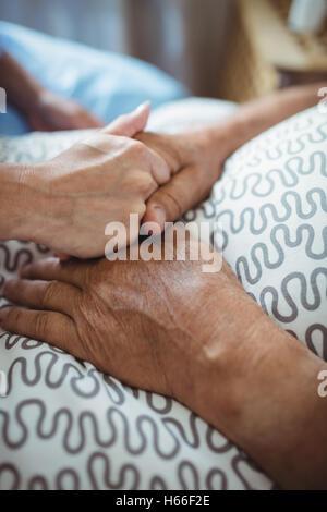 Nurse holding hands of senior woman