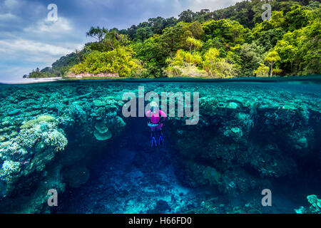 Split image shot of blond female scuba diver exploring coral reef with tropical island in background - Stock Photo