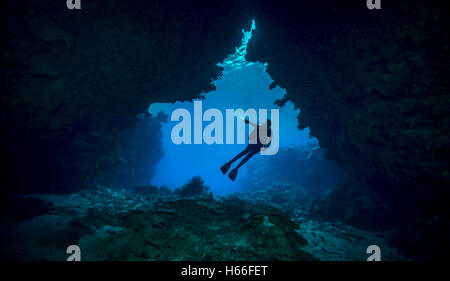 Scuba diver enters underwater cave system - Stock Photo