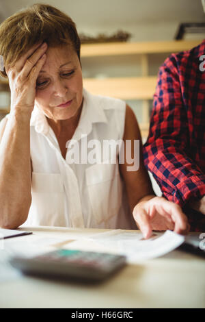 Worried senior woman looking at bills - Stock Photo