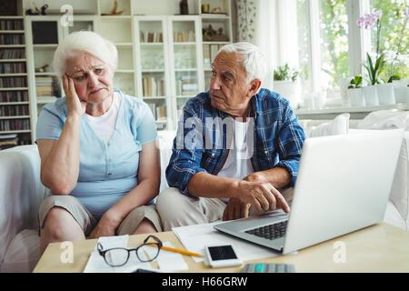 Worried senior couple using laptop - Stock Photo