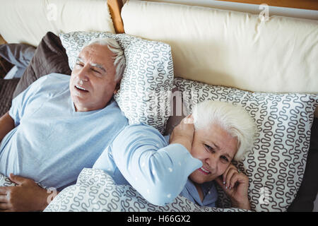 Man snoring and woman covering her ears while sleeping on bed - Stock Photo