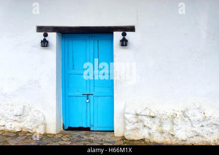 View of old wooden door on white colonial building in Villa de Leyva, Colombia - Stock Photo