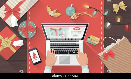 Man purchasing Christmas gifts online using a laptop on his desk, shopping bags and decorations all around, holiday - Stock Photo
