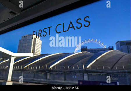 First Class sign on window of railway carriage pulling into London Waterloo with Shell Building and London Eye in - Stock Photo