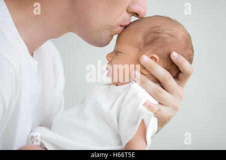 Portrait of man kissing his baby - Stock Photo