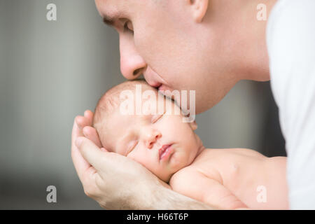 Young man kissing a newborn, he holds in his palms - Stock Photo