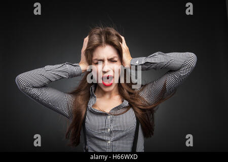 Woman screaming because of headache. - Stock Photo