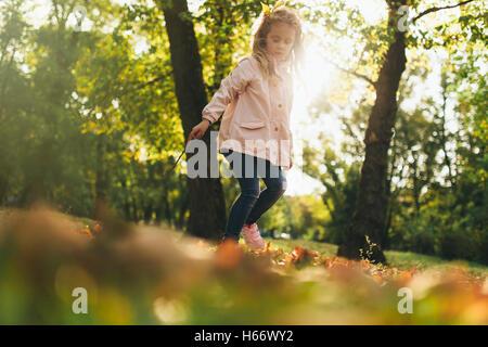 Happy child girl having fun in autumn park - Stock Photo