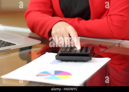 Closeup of a businesswoman hands accounting with calculator sitting in a desktop at office with her red suit in - Stock Photo