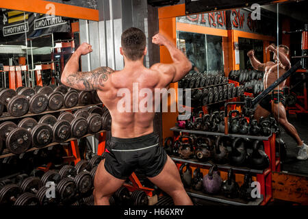 bodybuilder doing competition poses and showing defined back and arm muscles - Stock Photo