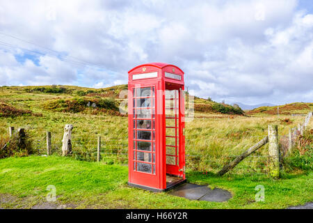 Red telephone box without a door in a remote rural location on the Isle of Skye Scotland - Stock Photo