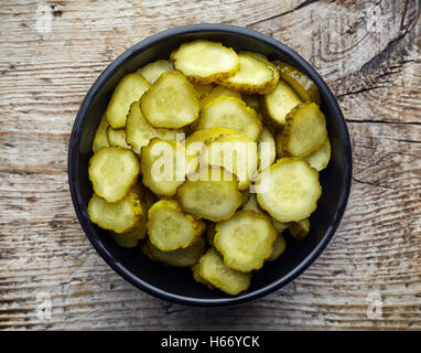 Bowl of chopped pickled cucumber on wooden background, top view - Stock Photo