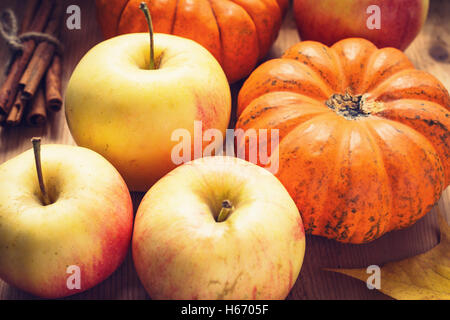 Autumn harvest: apples, pumpkins and bunch of cinnamon sticks on wooden table. Seasonal harvest. Toned image - Stock Photo