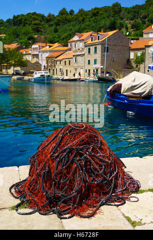 SUDURAD, CROATIA - JUNE 27, 2015: Scene of the fishing port, with a fishing net, boats, locals and tourists, in - Stock Photo