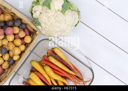Raw cauliflower head beside purple, red and yellow carrots and potatoes over white wooden background - Stock Photo
