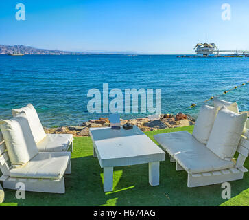 The cozy white benches in the beach cafe on the seashore with the view on the dive station, Eilat, Israel. - Stock Photo