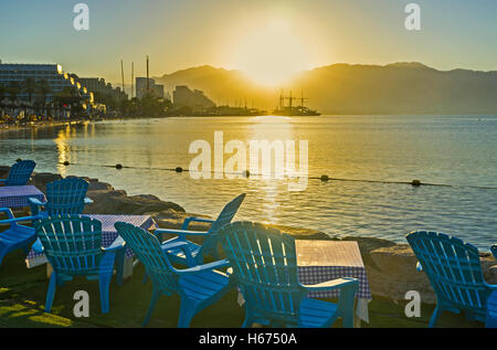 The beach cafe is the best place to watch the bright sunshine over Aqaba Gulf, Eilat, Israel. - Stock Photo