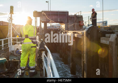 crew working on Caledonian MacBrayne ferry Loch Bhrusda as it docks at Mallaig dock at the end of its crossing from - Stock Photo