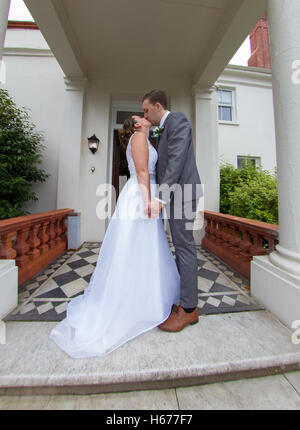 Bride and groom kissing on the steps of their wedding venue. Full length shot of the newly wed husband and wife - Stock Photo