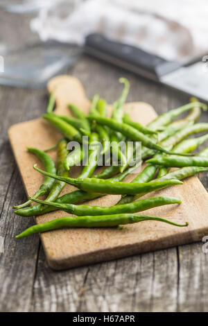 Green chili peppers on cutting board. - Stock Photo