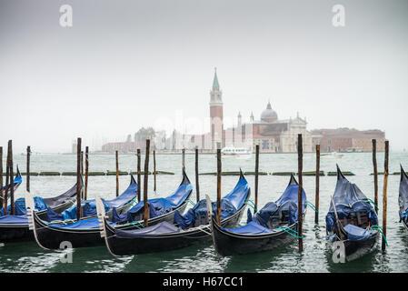 A row of gondolas parked beside the Riva degli Schiavoni in Venice.The Church of San Giorgio Maggiore on island - Stock Photo