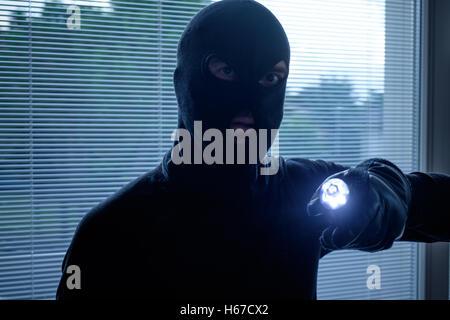 Burglar wearing a balaclava holding a flashlight - Stock Photo