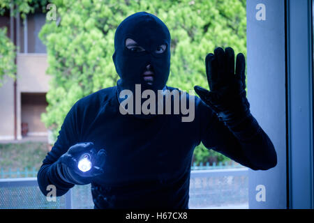 Burglar wearing a balaclava looking through the house window - Stock Photo