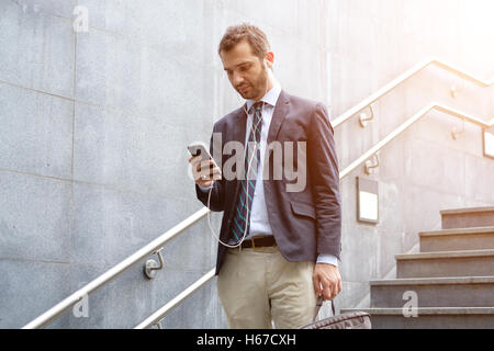 Successful businessman looking on his smartphone in the city street - Stock Photo