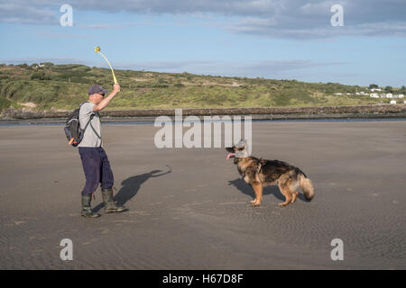 Man throwing a ball for his dog on the beach at Poppit Sands near Cardigan, Wales. They are having fun playing a - Stock Photo