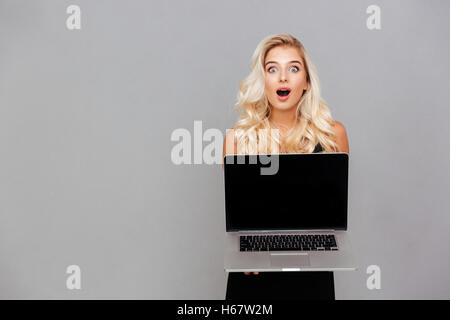 Portrait of a happy excited woman pointing finger on blank laptop computer screen isolated on a white background - Stock Photo