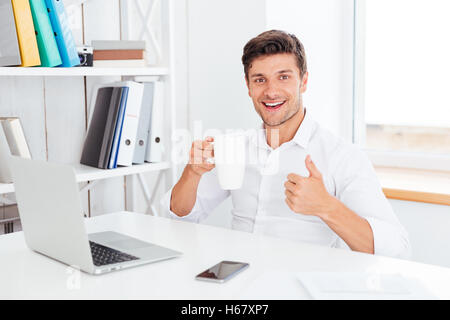 Happy smiling businessman holding tea cup and showing thumbs up while sitting at the office desk - Stock Photo