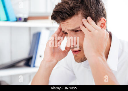 Close up portrait of a tired young businessman touching his temples and having a headache in office - Stock Photo