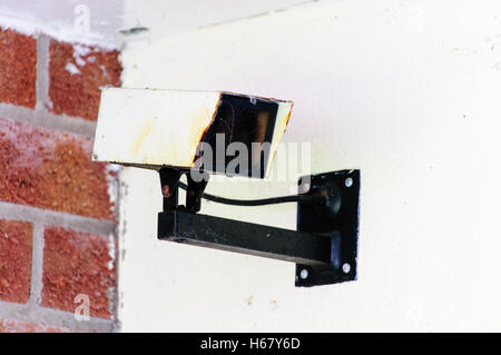 A rusty, old CCTV camera on the wall of a house - Stock Photo