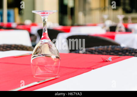 Wine glass upside down on a restaurant table with a red tablecloth - Stock Photo