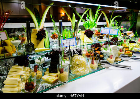 Large selection of cheese with ornate decoration at the buffet of a hotel restaurant - Stock Photo
