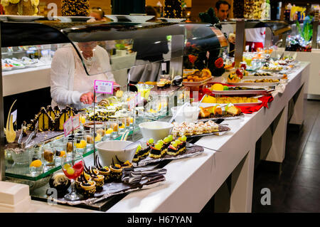Dessets consisting of cakes, mousses and fruit at the buffet of a hotel restaurant - Stock Photo