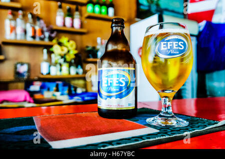 Turkish Efes pilsner lager beer on the counter of a bar in Turkey. - Stock Photo