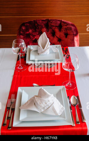 Folded napkin and place settings in a fine dining restaurant - Stock Photo