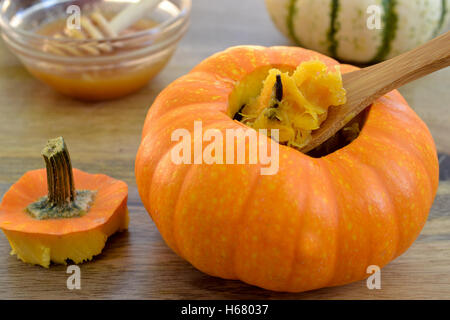 Two stuffedbaked mini-pumpkins  with spiced pumpkin puree, served with honey, on green dishcloth and wooden table, - Stock Photo