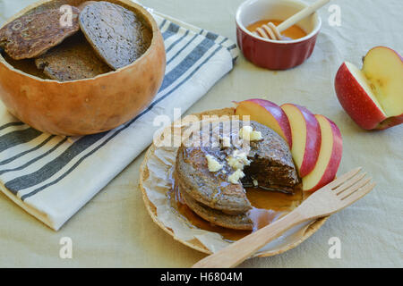 Rustic meal of buckwheat pancakes in plate and bowl made of gourds, on flower sac tablecloth, accompanied by maple - Stock Photo