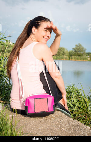 Portrait of young lady in pink shirt with handbag siting by the lake - Stock Photo