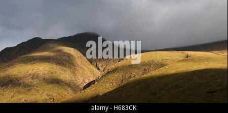 Rain cloud forming thick fog descending from steep mountainside bading in evening light, Glen Coe, Scottish Highlands, - Stock Photo