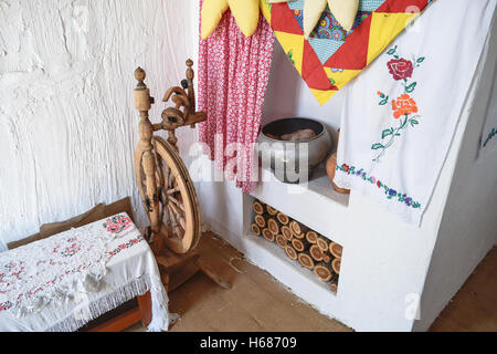 Interior Cossack home. Spinning Wheel, oven, kettle, firewood oven and whitewashed walls - Stock Photo