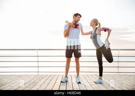 Young beautiful couple doing sports exercises at the beach pier - Stock Photo