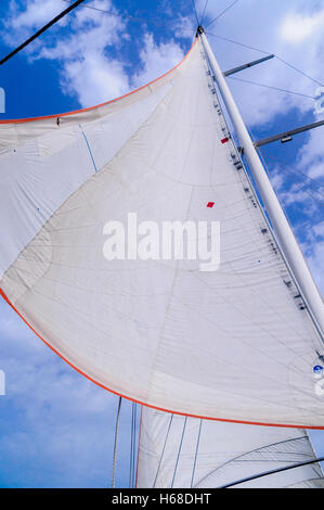 White canvas sails of a sailing ship against a blue sky with some clouds. - Stock Photo